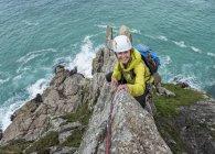 Mujer sonriente de Reino Unido, Cornwall, escalada en cresta de comando - foto de stock