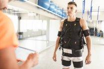Mann, training mit elektrischer Muskelstimulation in Turnhalle überwacht von Mann mit tablet — Stockfoto