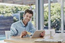 Ritratto di uomo sorridente con tavoletta a tavola — Foto stock