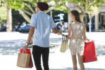 Молоді пара ходьбі сумками разом холдингу міській вулиці — стокове фото