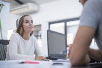 Bureau assis avec ordinateur portable dans le bureau et discuter du projet — Photo de stock
