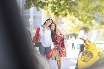 Mãe e filha juntamente com sacos de compras, andando na rua da cidade — Fotografia de Stock