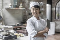 Portrait of young confident female chef in cooking class — Stock Photo