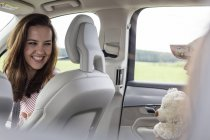 Mother looking at daughter playing with teddy bear in car — Stock Photo