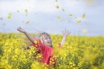 Ragazzina felice in piedi in campo stupro gettando fiori in aria — Foto stock