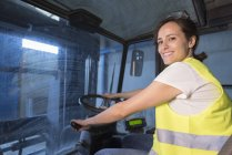 Woman driving a forklift in factory hall — Stock Photo