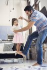 Father playing with daughter at home rising her on his leg — Stock Photo