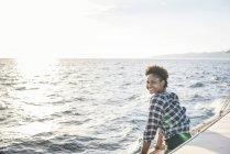 Улыбающаяся молодая женщина на лодке смотрит в камеру — стоковое фото