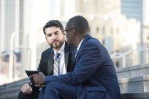 Deux hommes d'affaires assis sur les escaliers parler et partager la tablette — Photo de stock