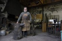 Portrait of confident blacksmith standing in workshop — Stock Photo