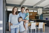 Portrait of smiling young family indoors — Stock Photo