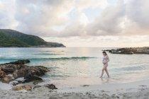 Femme enceinte marchant sur la plage avec un ciel nuageux sur fond — Photo de stock