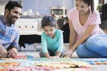 Feliz familia sentada en el suelo y jugando con su hija - foto de stock