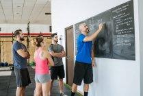 Coach in a fitness class writing on blackboard — Stock Photo