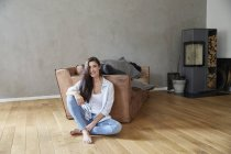 Smiling woman sitting on wooden floor at home — Stock Photo
