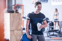 Smiling caucasian young man in gym — Stock Photo