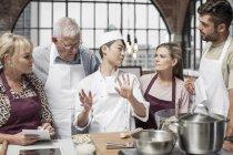 Küchenchef am Tisch beginnt Kochkurs mit erwachsenen Lernenden — Stockfoto