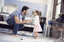 Отец, играя с дочерью дома на диване — стоковое фото