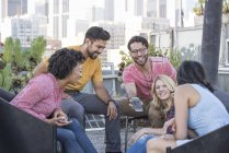 Friends looking at smartphone at rooftop party, Los Angeles, USA — Stock Photo