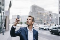Germany, Berlin, businessman taking picture with smartphone — Stock Photo