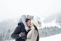 Couple with daughter kissing in winter landscape — Stock Photo