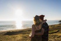 Rückansicht des jungen Paares am Meer bei Sonnenuntergang — Stockfoto