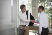 Caucasian men greeting in modern office — Stock Photo
