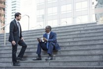 Two smiling businessmen talking on stairs — Stock Photo