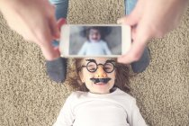 Mother taking photo of her daughter with smartphone — Stock Photo