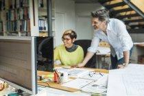 Mâles et femelles architectes discutant travailler au bureau — Photo de stock