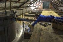 Worker repairing tanks in whiskey distillery — Stock Photo