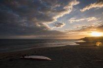 Spanien, Teneriffa, Surfbrett am Strand bei Sonnenuntergang — Stockfoto