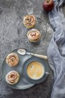 Filo pastry apple cakes in rose shape with cup of coffee on grey tabletop — Stock Photo