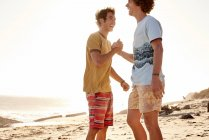Deux jeunes hommes heureux sur la plage — Photo de stock