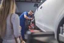 Meccanico di montaggio pneumatico dell'automobile in officina — Foto stock