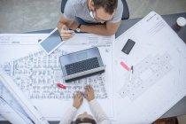 Два дизайнера обсуждают совместный проект с чертежами и ноутбуком — стоковое фото