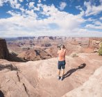 USA, Utah, Young man standing on Dead Horse Point photographing Colorado River — Stock Photo
