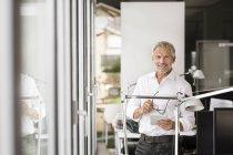 Бизнесмен, держащий планшет в офисе — стоковое фото