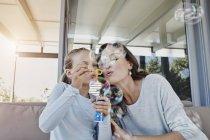 Porträt der Frau mit Tochter bläst Seifenblasen — Stockfoto