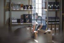 Stock de asistente masculino tomar botellas de vino y cajas de - foto de stock