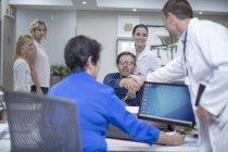 Пацієнт в інвалідному візку привітання лікаря на стійці реєстрації в лікарні — стокове фото