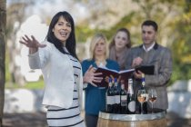 Wine saleswoman talking with group of clients outdoors — Stock Photo