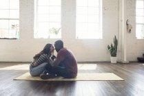 Giovani coppie che stringe a sé che si siede sul tappeto in un loft — Foto stock
