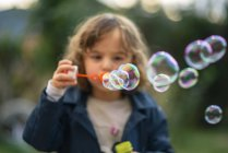 Little girl blowing soap bubbles — Stock Photo