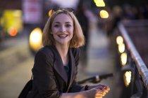 Junge, attraktive blonde Frau posiert vor verschwommenen Hintergrund — Stockfoto