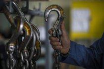 Close-up do trabalhador da fábrica segurando gancho de aço industrial — Fotografia de Stock