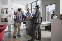 Uomo di affari che agitano le mani con i client in ambiente di ufficio di città — Foto stock