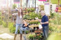 Gardener helping clients at garden centre — Stock Photo