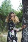 Усміхаючись блондин жінці носити плаття з квіткового дизайну — стокове фото