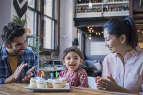 Familia feliz en mesa con tortas de cumpleaños de la taza - foto de stock
